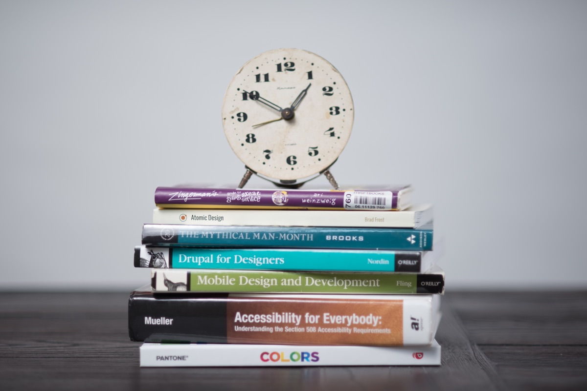 An analog clock atop a stack of the Gravity Works team's favorite books
